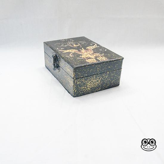 Imagen lateral de las cajas. Color negro y purpurina. Acabado barniz brillo